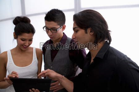 three young businesspeople using digital tablet