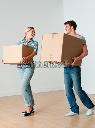 young couple carrying cardboard boxes