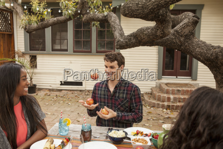 friends sitting around table sharing barbecue