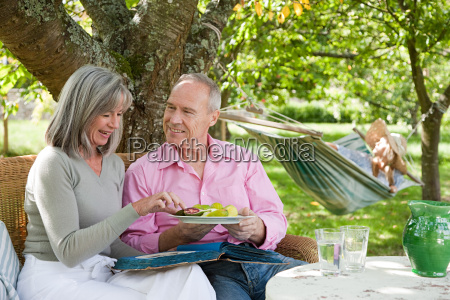 mature couple eating from plate of