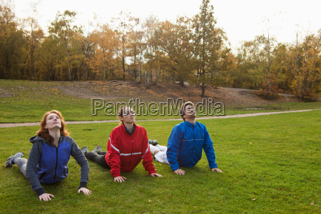 three young friends stretching on grass