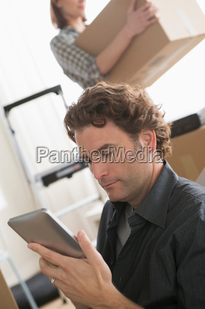 man looking at digital tablet whilst