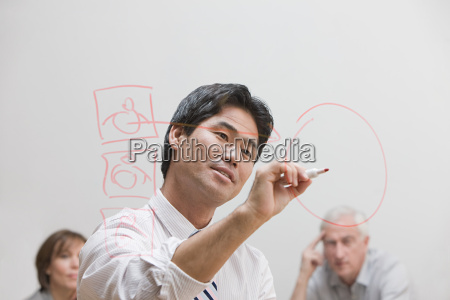 man drawing diagram on glass wall
