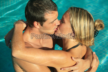 young couple kissing in swimming pool
