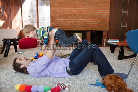 father lifting son in living room