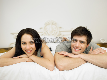 young couple lying on bed portrait