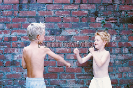 boys fighting against wall
