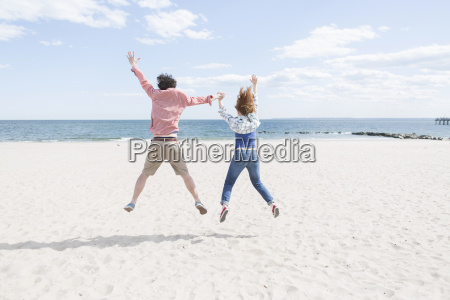 rear view of couple jumping mid
