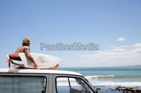 mature male surfer watching from vehicle