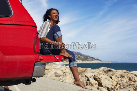 young woman sitting on car hood