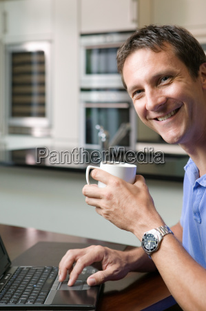 man with laptop and coffee cup