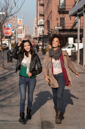 women walking together on city street