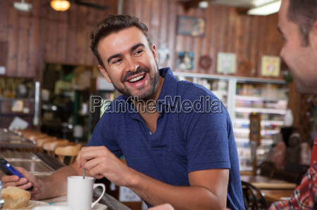 two male friends chatting at restaurant
