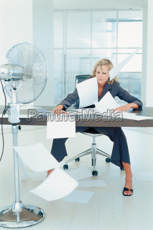 businesswomans paperwork blowing in the air