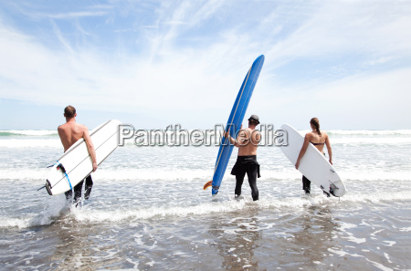 male and female surfer friends standing