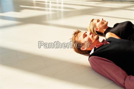 man and woman lying on floor