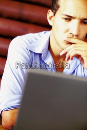 man using laptop computer in bar