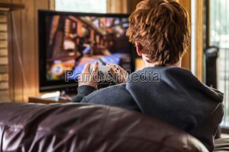 teenager spielt videospiele zu hause