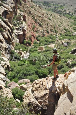 female hiker standing on rock mount