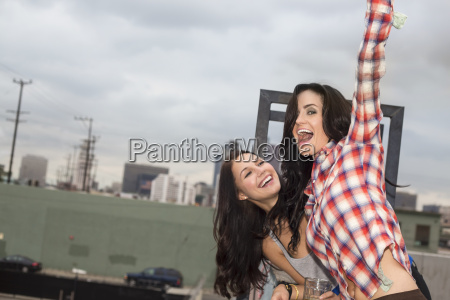 two female friends jumping around at