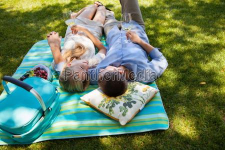 young couple lying on picnic blanket