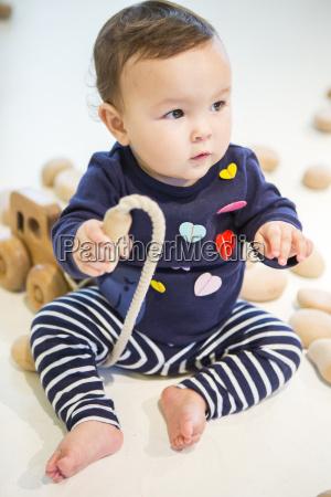 baby girl sitting on floor with