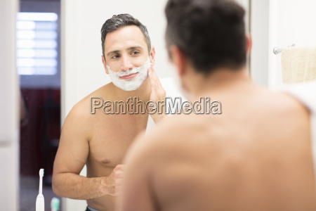 mid adult man looking in mirror