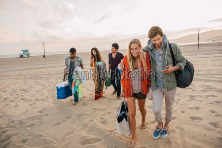 grupa przyjaciol spaceru wzdluz plazy mloda