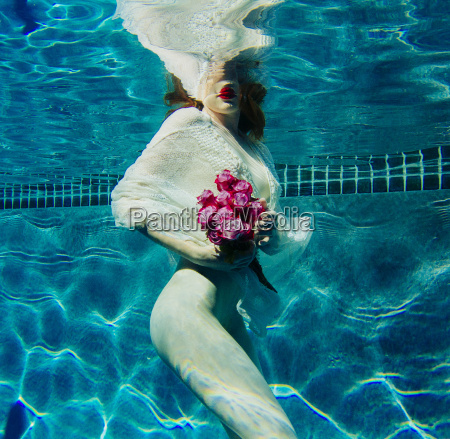 young woman underwater wearing thin white