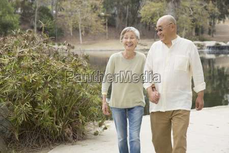 senior couple walking along pathway holding