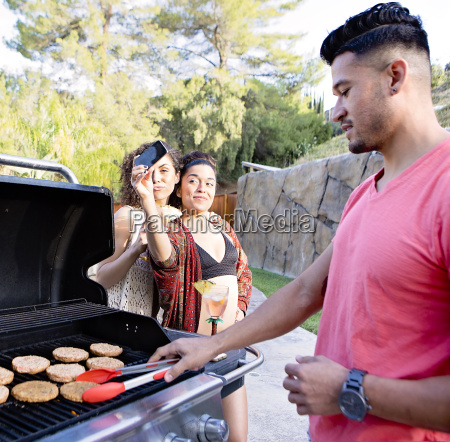 young man cooking on barbecue in