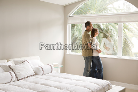 couple looking out of bedroom window