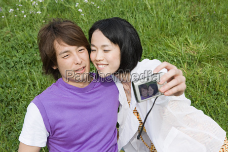 young couple on field with camera