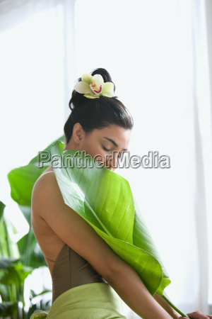 young woman holding a large leaf