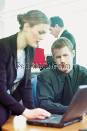 businessman and businesswoman using laptop in