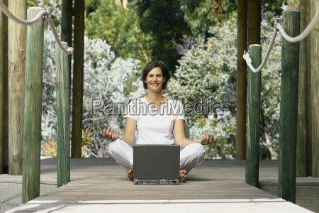 woman with computer doing yoga