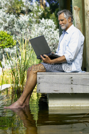 man beside pool with computer