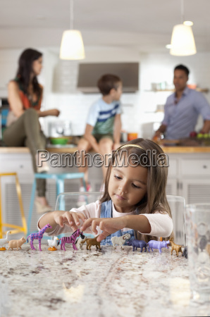 girl playing with toy animals