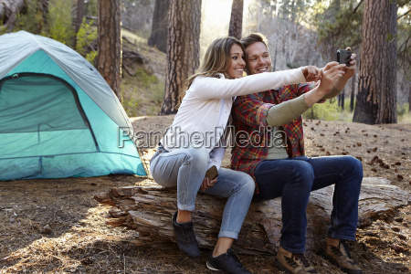 young camping couple taking smartphone selfie