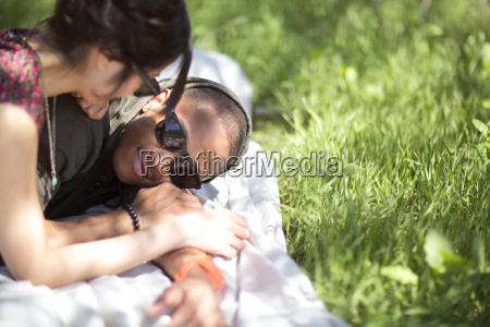smiling young couple on picnic blanket