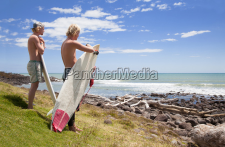 two young male surfer friends watching