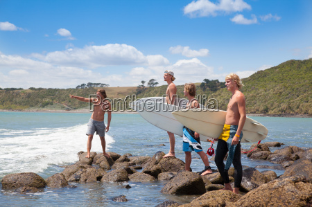 four young male surfer friends pointing
