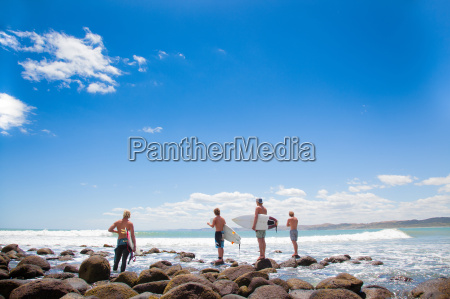 four young male surfer friends watching