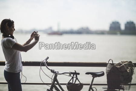 mid adult woman cyclist photographing with