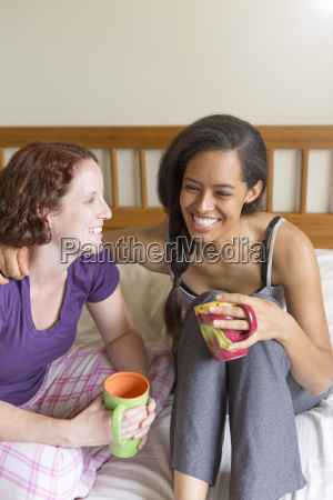 young women sitting on bed arm