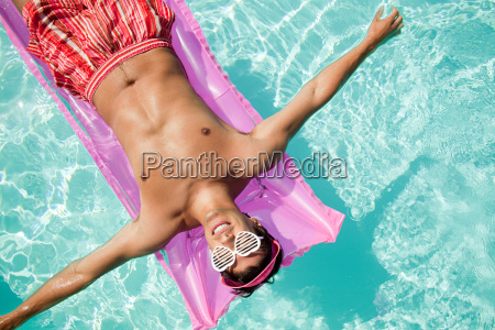 man on inflatable mattress in pool