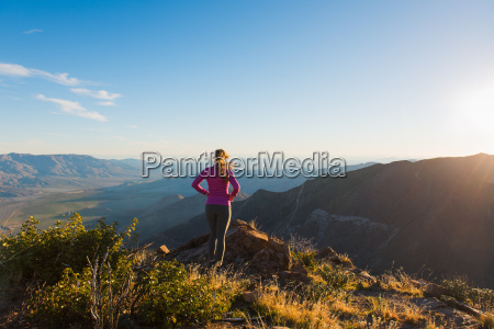 young female trail runner looking at