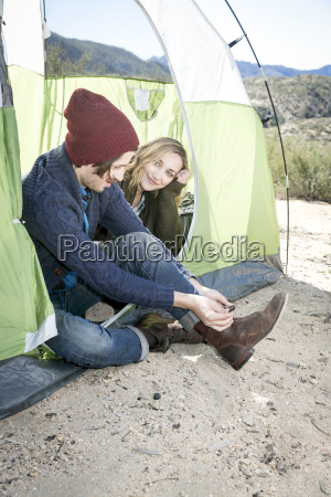 young couple sitting in tent young