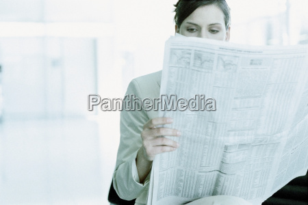 businesswoman reading a paper in airport