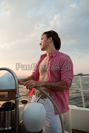 mid adult man steering yacht